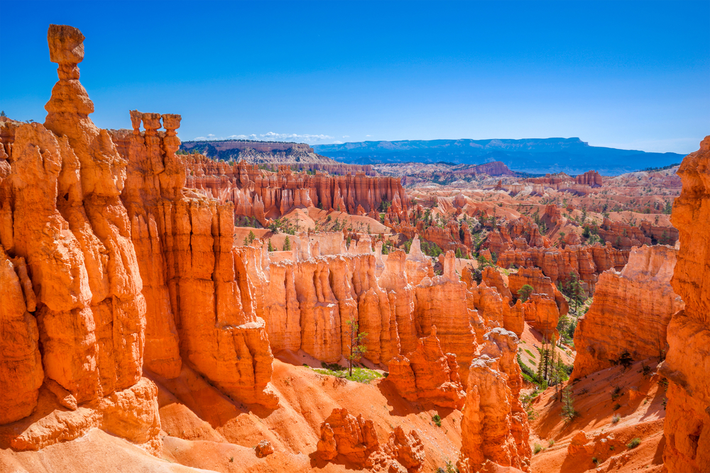 The large red sandstone rock formations looking down the valley of Bryce Canyon. In the distance you can see more red sandstone rock formations and mountains. One of the best Southwest road trip stops.
