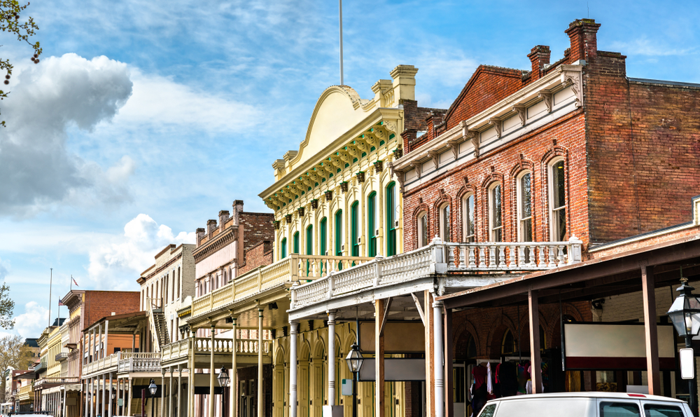 A row of old buildings that date back to the California gold rush in Old Sacramento. They are brick, have decks on the front of them, and one is painted pale yellow and green.