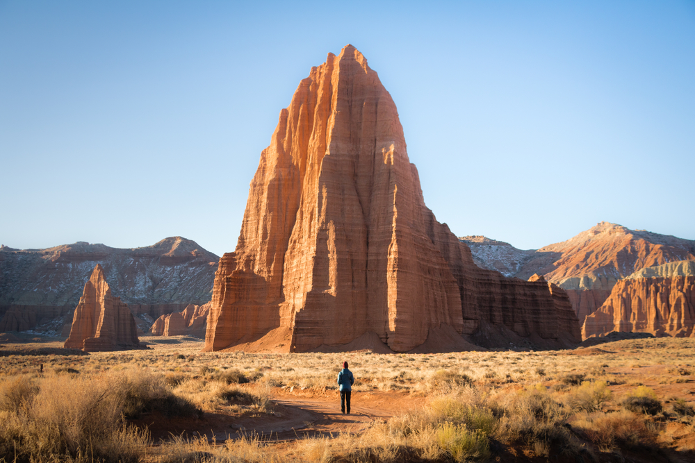 The large Temple Sun rock formation at Capitol Reef National Park. It is a light orange rock formation that is taller than the other mountains and rocks near it.  There is a person in dark clothes standing in front of it and they look very small.