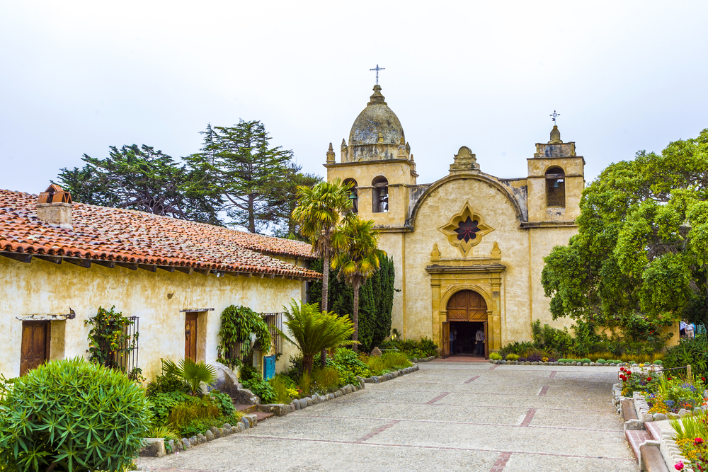 The exterior and courtyard of the historic Carmel Mission. It is an old Spanish style mission with Spanish colonial architecture. A great starting point for a Big Sur road trip