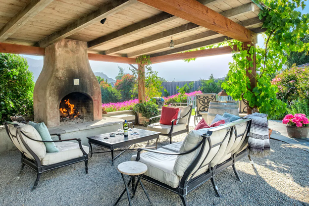 The private patio with seating, a fireplace, and covered pergola with vines growing on it. There are pots of pink flowers around the patio.