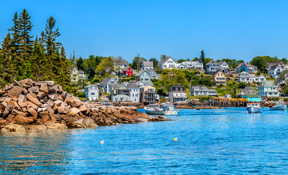 Looking at a charming town from the water in Coastal Maine. The town is right on the water and has colorful homes and boats in the water. You can also see some of the rocky shore with trees on it.