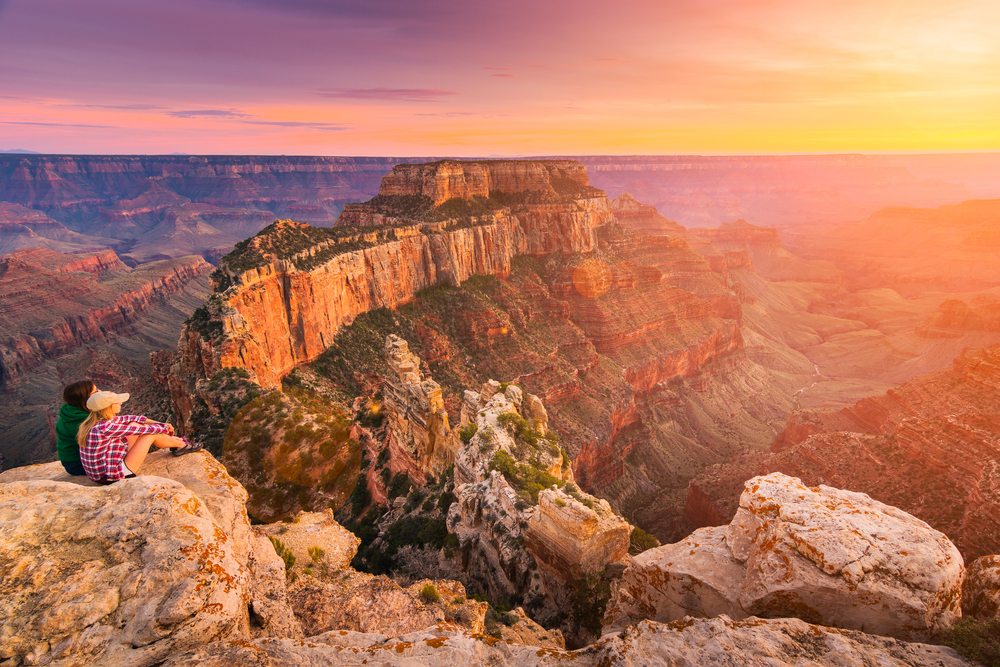 A couple sitting on a rock looking out at the north ridge of the Grand Canyon. It is sunset and the sky is orange, yellow, pink, and purple. A great Southwest road trip stop.