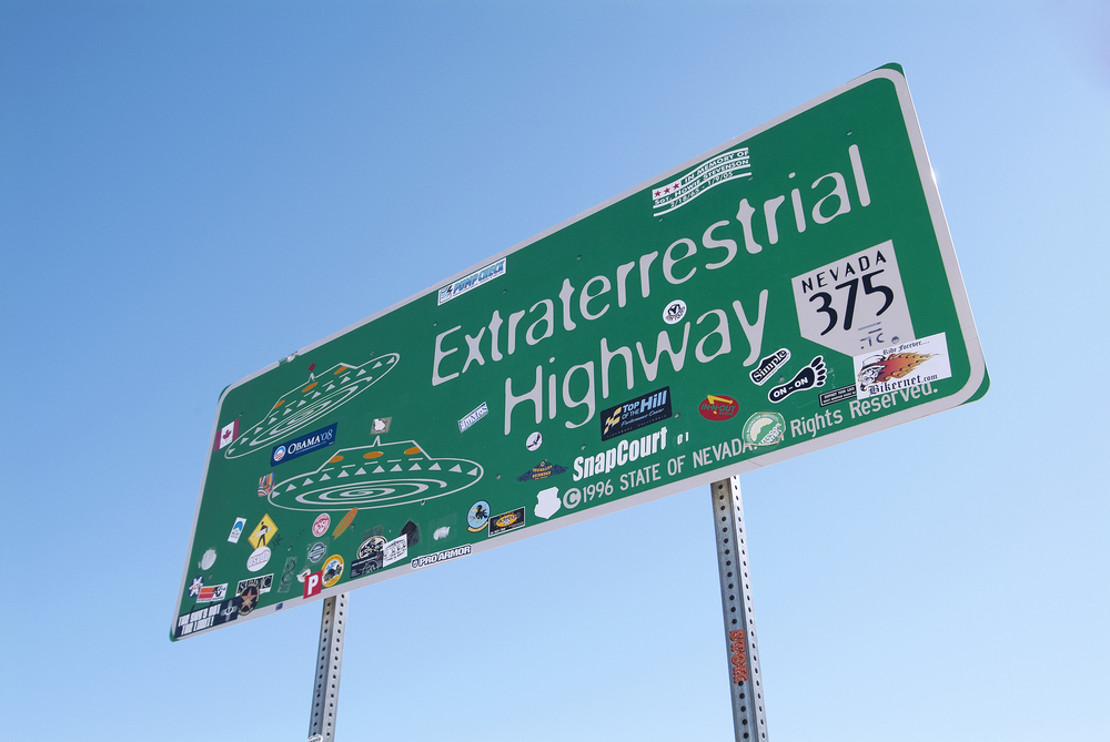 The highway sign for the Extraterrestrial Highway in Nevada. the sign uses the 'X-files' font and has UFOs on it. It has also been covered by stickers.
