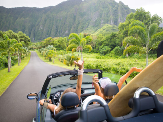 women in car in Hawaii with surfboards