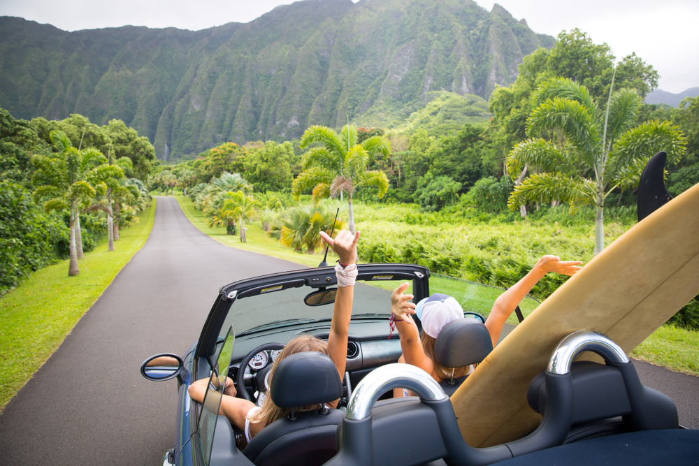 Two women with their hands up riding in a car with the top down and a surf board in the back seat. They are driving on a road in Hawaii surrounded by greenery and palm trees. In the distance you can see a large tropical style mountains. One of the best bachelorette party destinations.