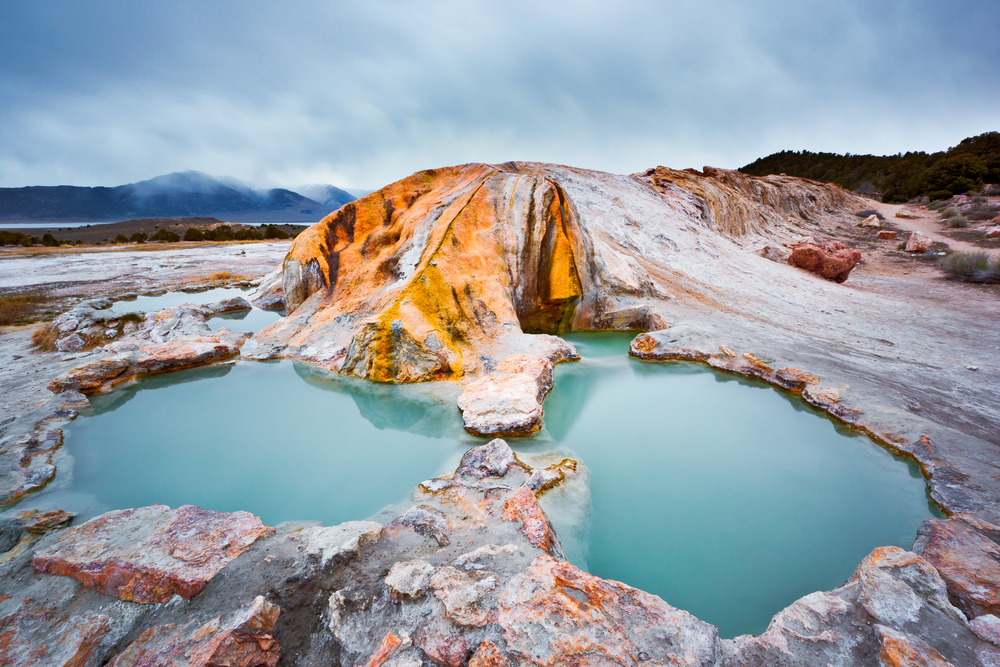 A natural hot spring in a rock formation. The area is full of smooth rocks and you can see mountains and trees in the distance. The water in the hot spring is a teal blue and there is steam in the air.