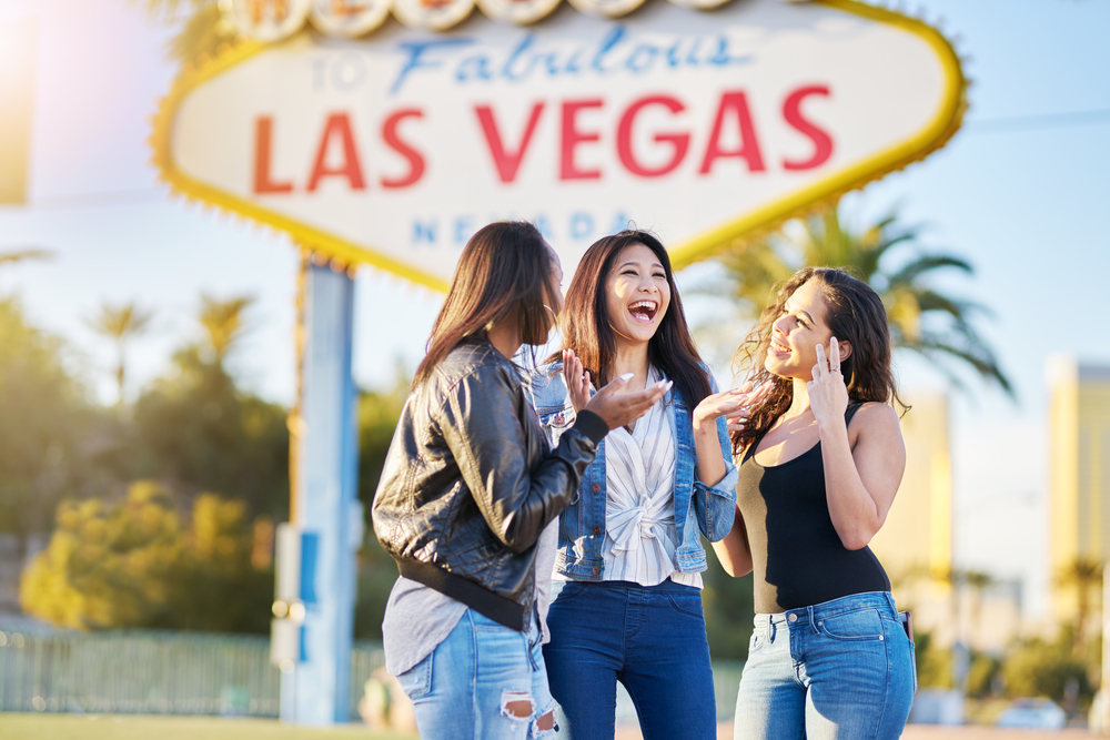 A group of three women laughing in front of the famous Las Vegas sign in Las Vegas. They are smiling and laughing with each other.
