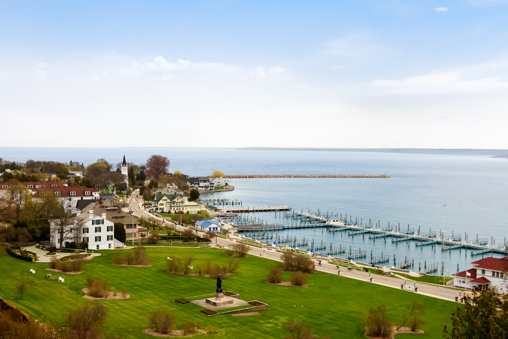 An aerial view of the harbor in Mackinac Island. You can see a green lawn, old buildings, and a large dock system but there are no boats in it.
