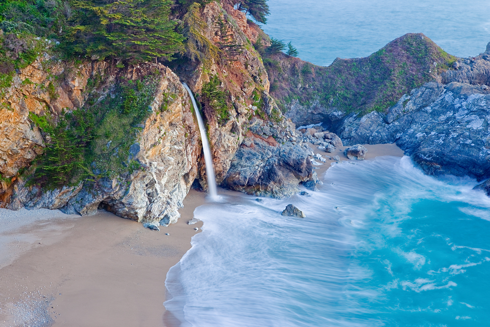 An aerial shot of the popular McWay falls, a large waterfall that flows directly onto a beach. The waterfalls comes from a large rock formation and the sand is pale tan and the water is a beautiful crystal blue.