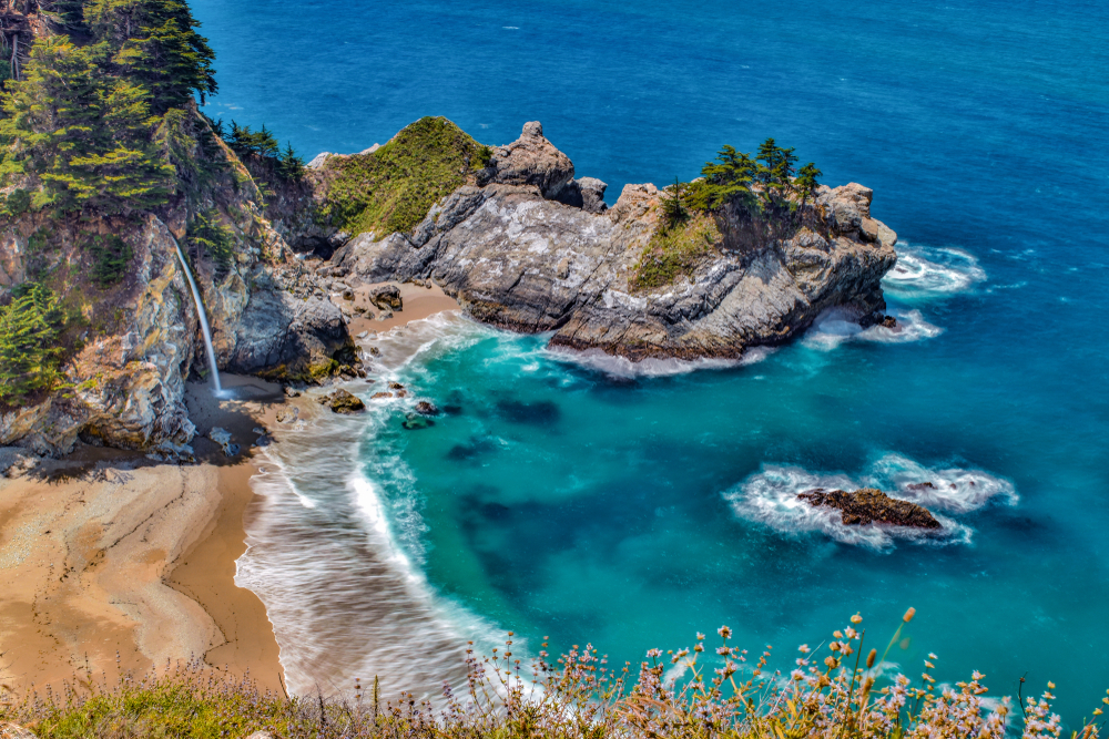 The view over the rocky cliffs to McWay Falls Cove. You can see the waterfall, large rock formations with trees growing on them, and the crystal blue pacific ocean.