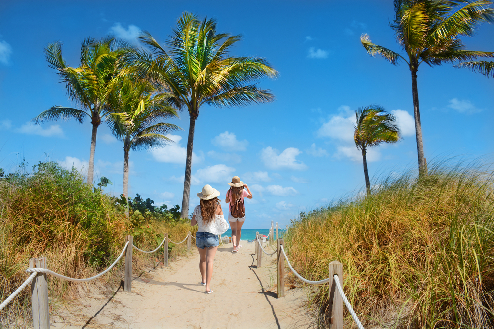 Two women in shorts and sun hats walking on a sandy path over the sand dunes towards the beach in Miami. The beach has large palm trees and you can see a glimpse of the crystal blue water