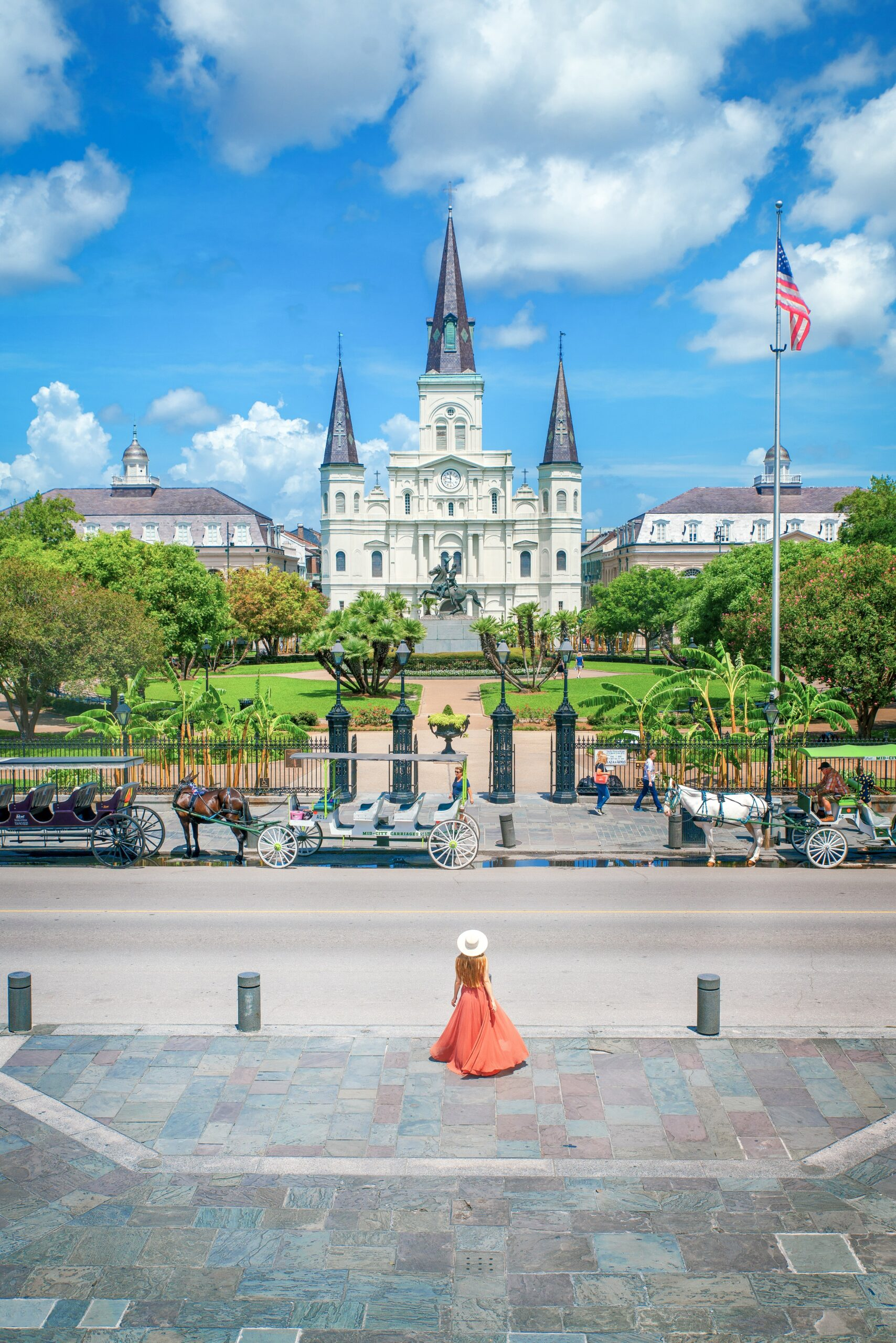 A woman in an orange maxi dress and white sunhat standing in Jackson Square in New Orleans on a sunny day.