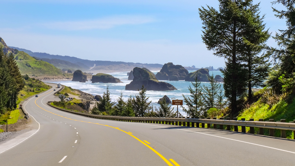 A highway on the Oregon coast. You can see large rock formations in the ocean and on the other side of the highway are green mountains. One of the best west coast road trip ideas.