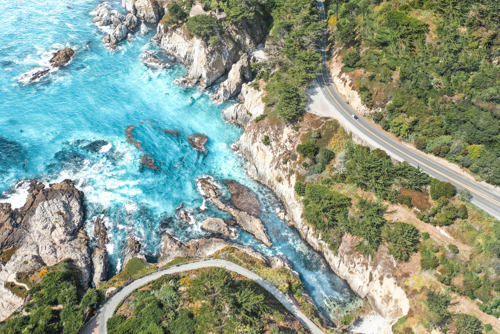 An aerial view of the winding Pacific Coast Highway with crystal blue water crashing around rocks, and the road is surrounded by rocky cliffs and greenery. One of the best west coast road trip ideas