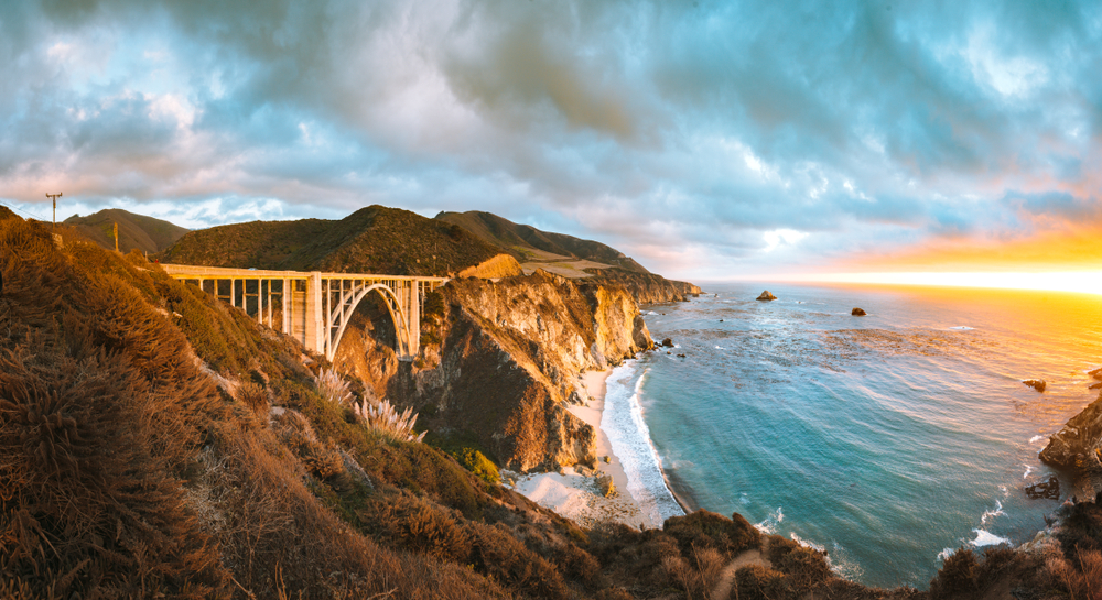 A panoramic of the Bixby Bridge at sunset. You can see the bridge, the rocky cliff side, and the pacific ocean. The sky is cloudy and the sun is bright orange. A popular stop on a Big Sur road trip