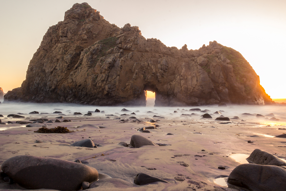 A large rock formation with a large door keyhole almost right in the middle of it. Around the rock formation is sand with large stones and puddles of water in it. There is a light fog on the ground and it is sunrise, so the sun is coming up behind the rock formation.