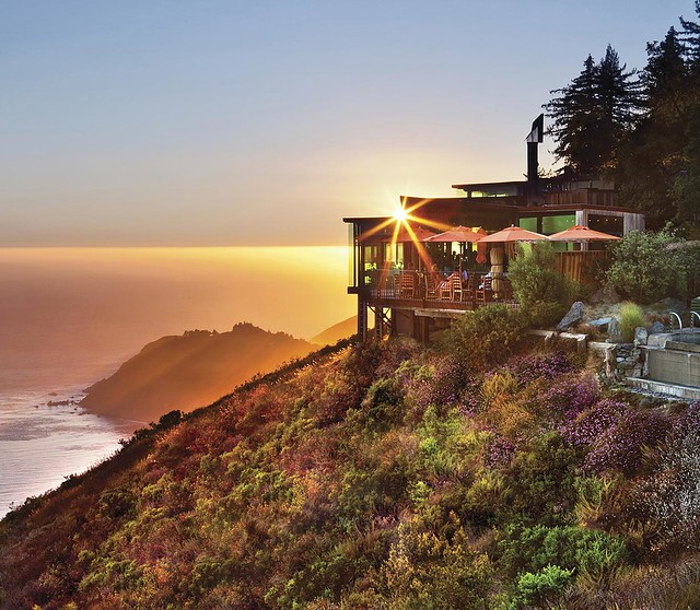 A luxury building on the side of grassy cliff over the Pacific Ocean. It is sunset, and behind the cliff you can see other rock formations. The building has a deck with patio tables and umbrellas on it and lots of windows.