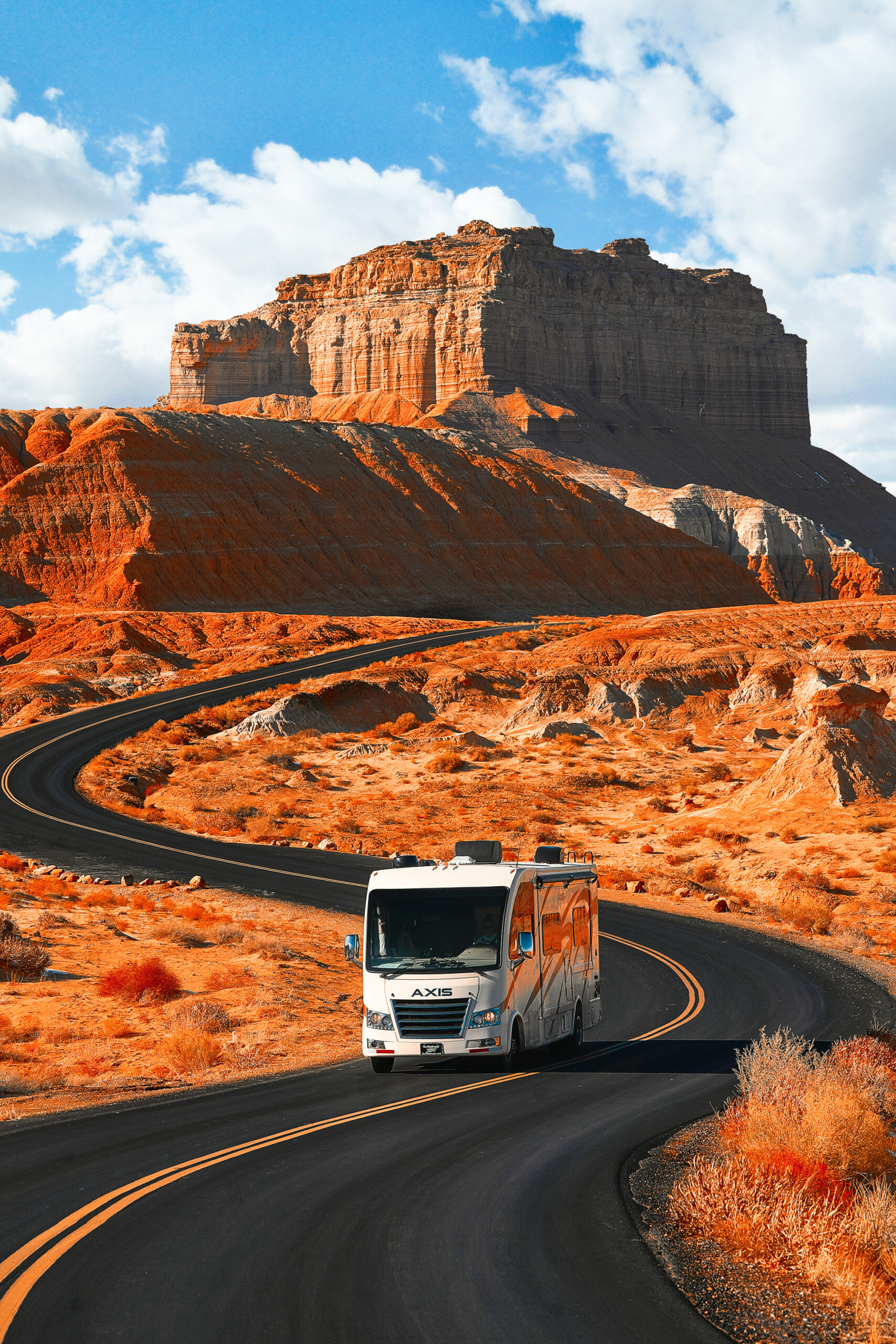 An RV driving through the red sandstone of the Southwest. In the background you can see a hill with a large red sandstone rock formation on top of it.