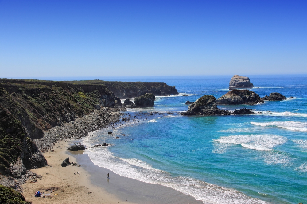 The view of the shore of Sand Dollar Beach in Big Sur from the top of the rocky cliffs. The shore is fairly sandy but there are large rocks on it. The ocean is bright blue and there are large rock formations in the water.