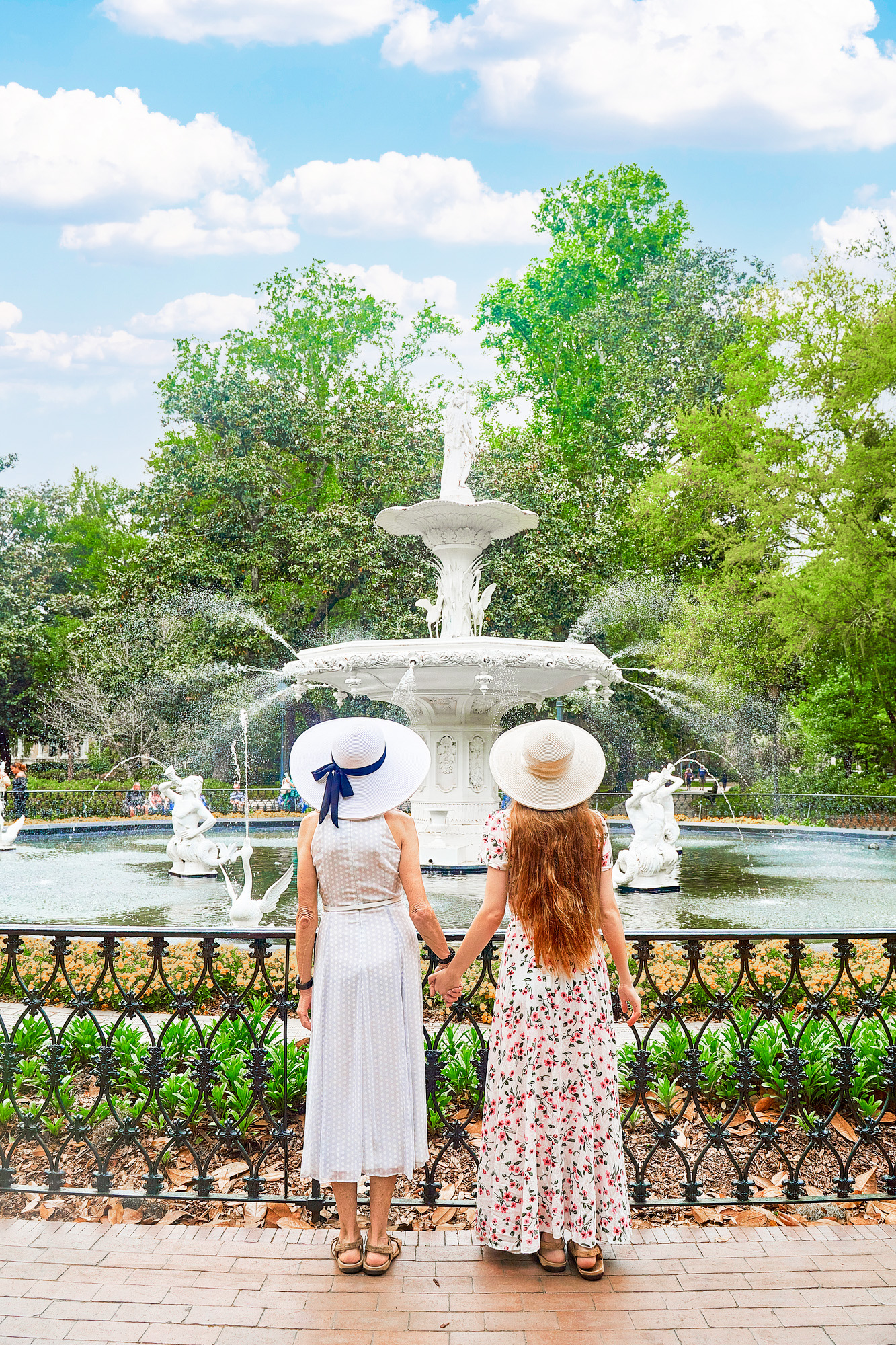 Two women in white sundresses and sun hats holding hands standing in front of Forsyth Fountain in Savannah Georgia, one of the best bachelorette party destinations.