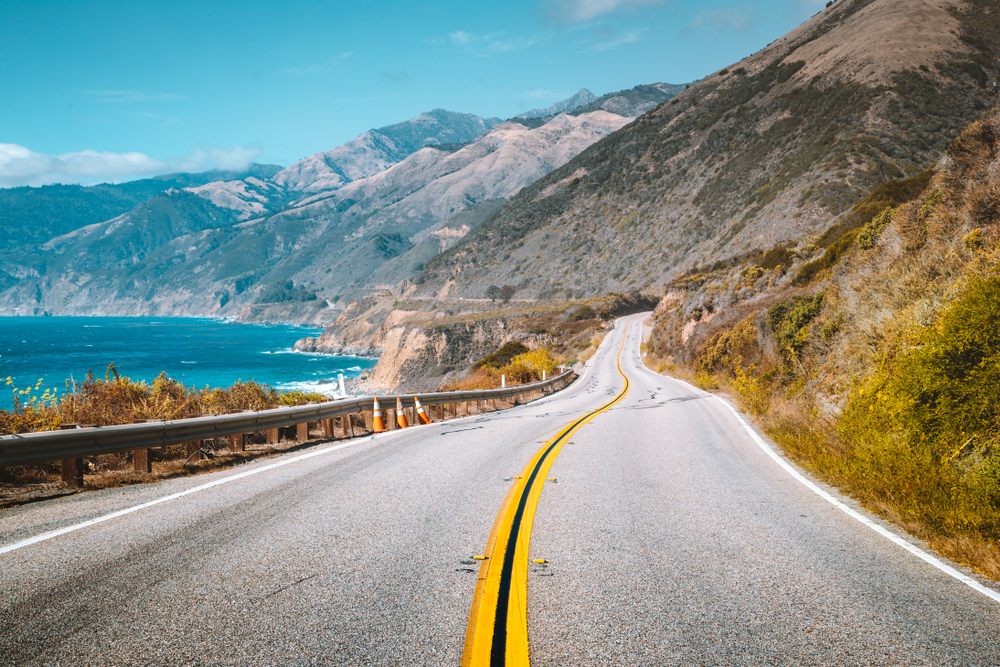 A scenic road on the coast of California. On one side of the road you can see a rocky shoreline and the pacific ocean. On the other side of the road are mountains that look very dry, almost like desert mountains.