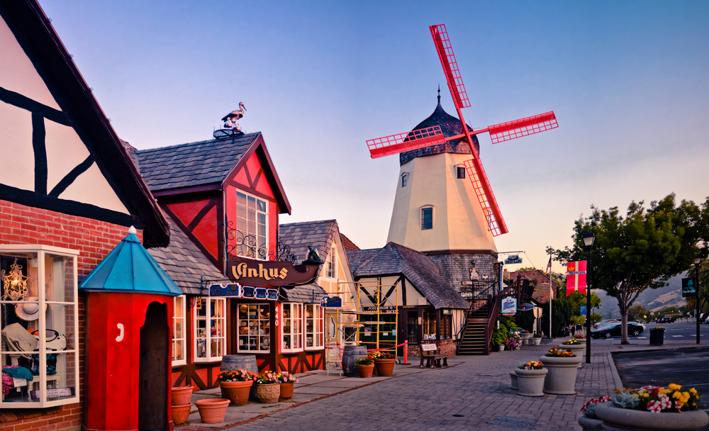 A street in Solvang California. It looks like a Dutch town with a windmill with red turbines, a cobblestone street, and charming buildings. It is one of the best west coast road trip stops.
