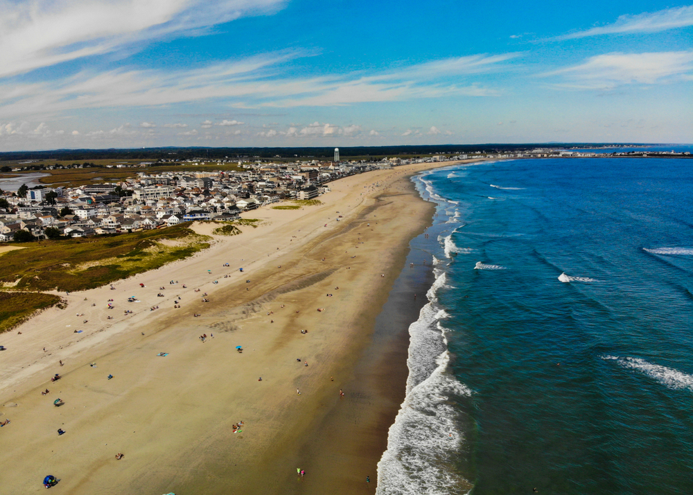 An aerial view of the shore of the Hamptons in Long Island. You can see people relaxing on the beach, large waves in the ocean, and homes behind the sandy shore. One of the best bachelorette party destinations.