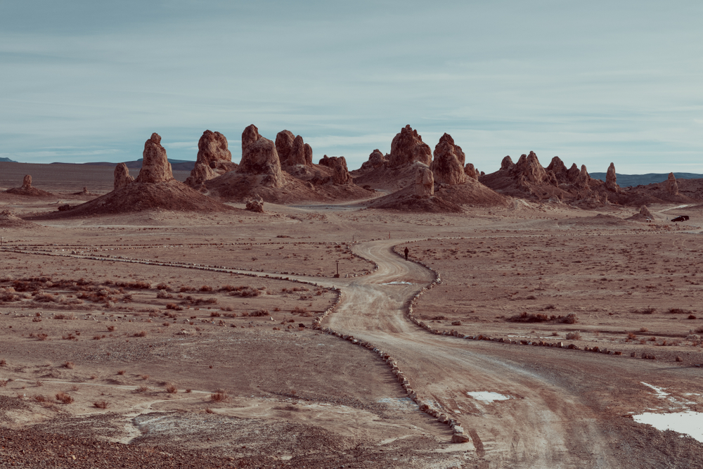 A dirt road in the middle of the desert that leads to the Trona Pinnacles. The Trona Pinnacles are large rock formations randomly in the middle of the desert.