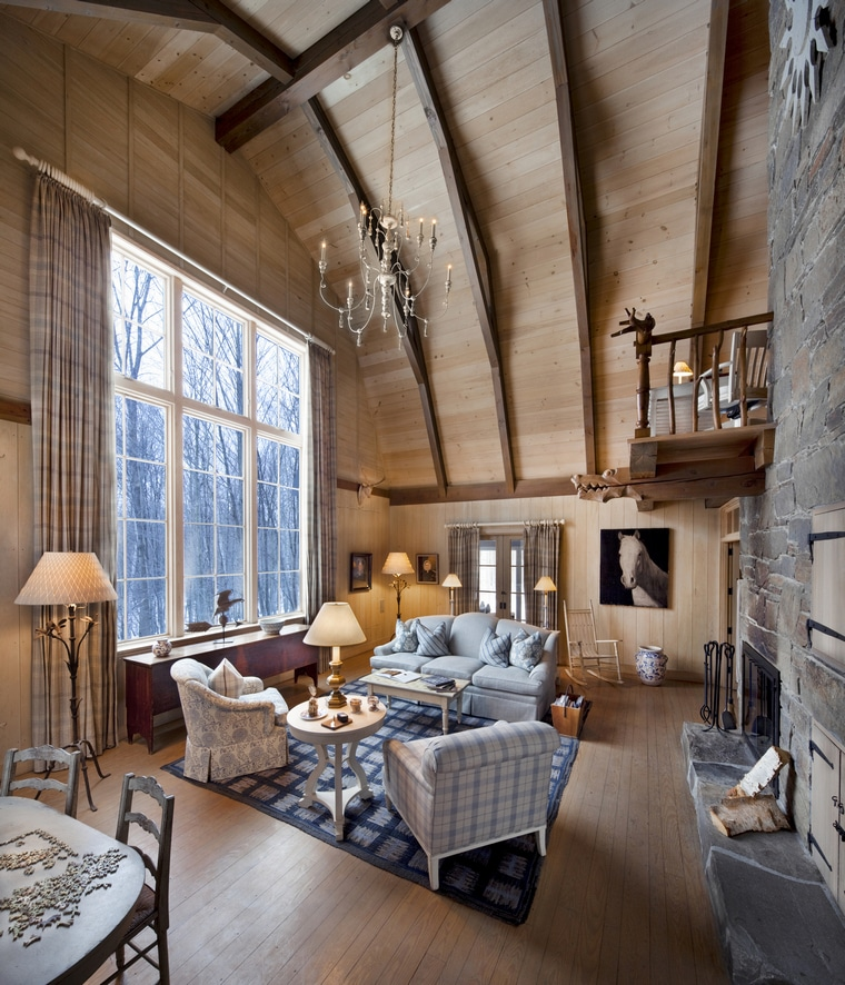 One of the cozy rooms at the Twin Farms resort in Vermont. It as a couch, two chairs, a fireplace, and lots of windows with tall ceilings and a chandelier hanging from the ceiling.