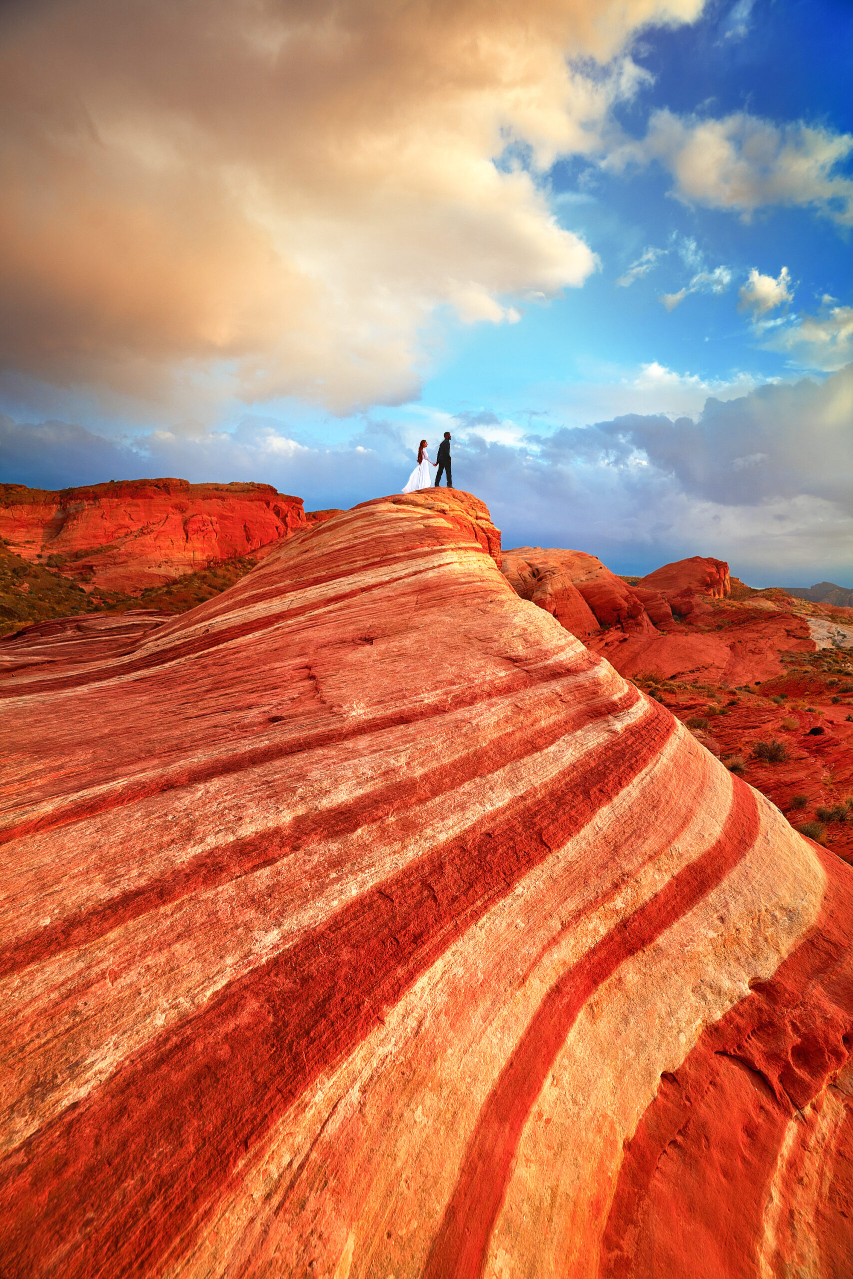 A woman in a white dress holding hands with a man in all black standing on a red and orange striped rock formation. The sky is blue and there are big fluffy clouds.