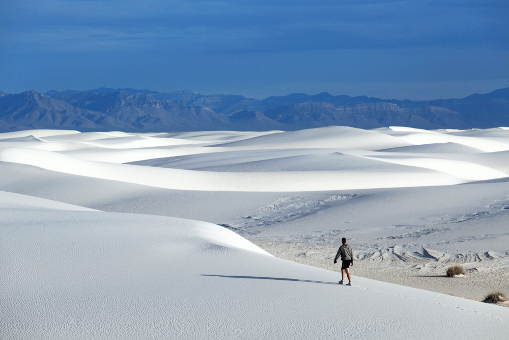 A person walking on the white sand dunes at White Sands National Monument in New Mexico.