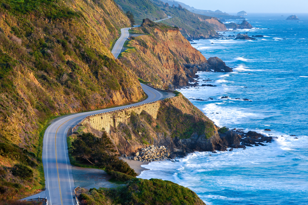 A view of Big Sur winding on the sides of the cliffs in the distance. On one side of the road is the pacific ocean and on the other side are rocky mountains with greenery. Part of the Big Sur road trip