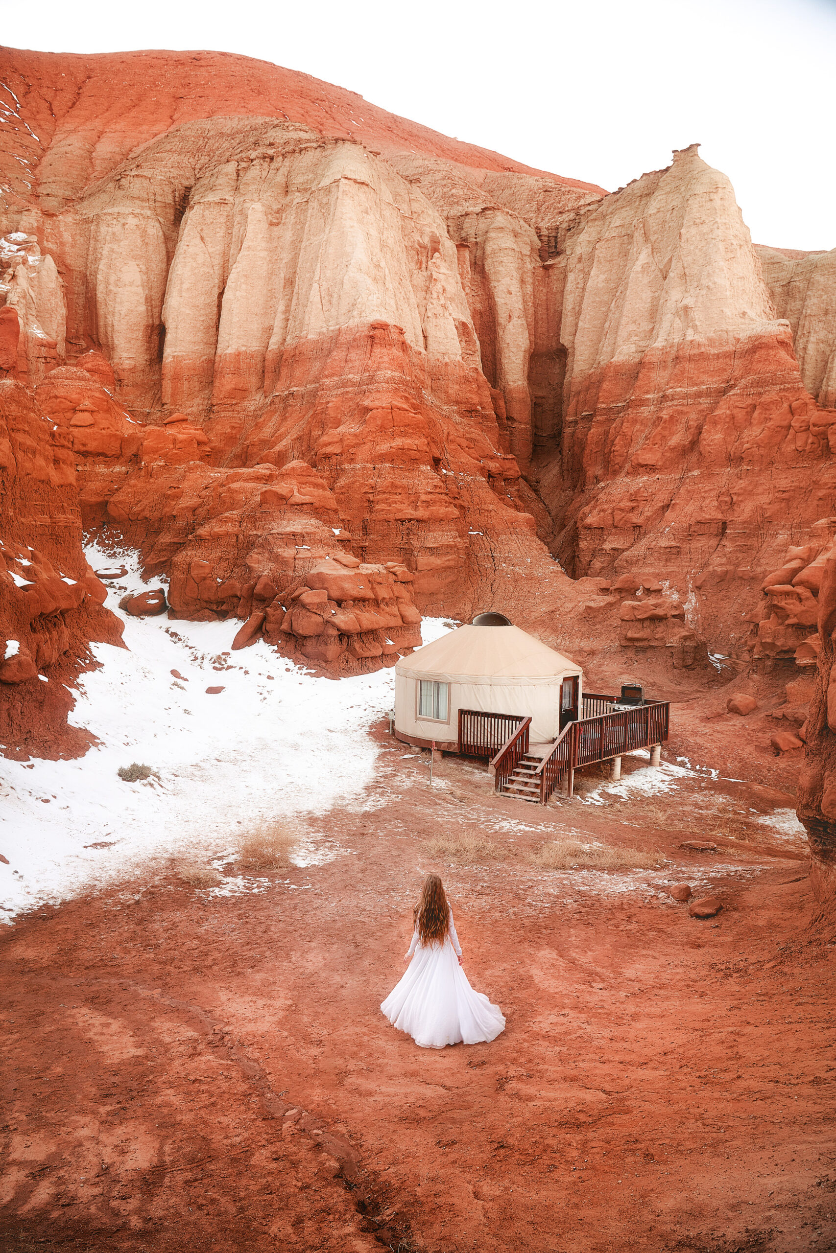 Looking down into a small valley where a woman is standing in a white dress with long hair. She is standing near a yurt. Behind the yurt you can see snow on the ground. A common view during a winter Southwest road trip