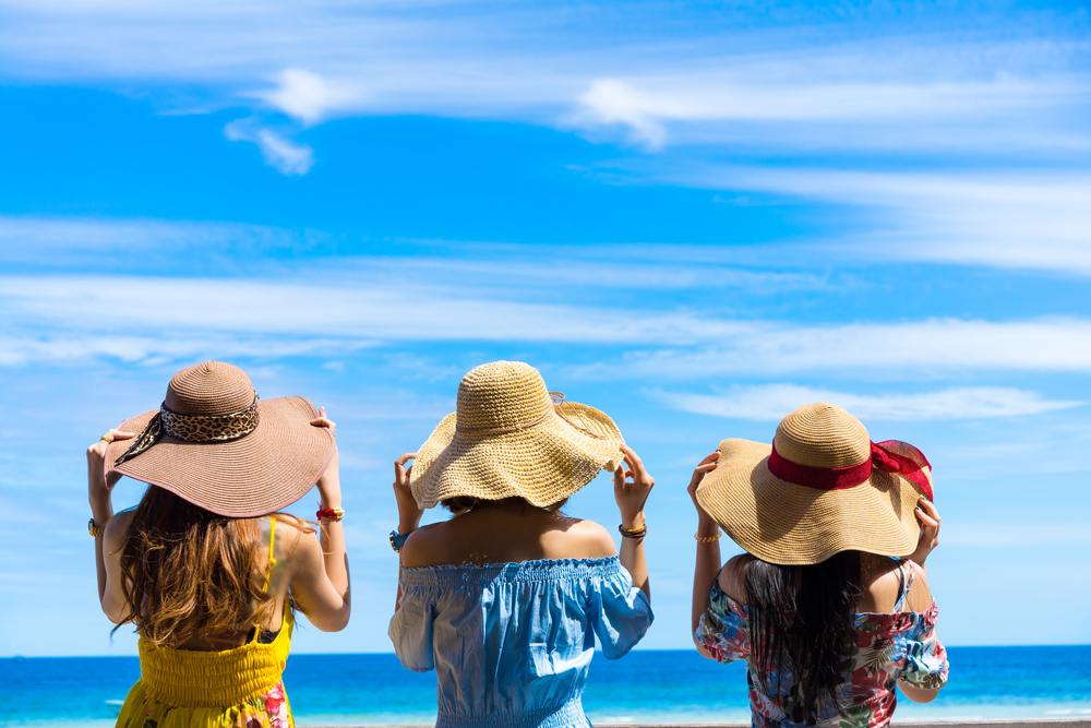 Three women standing next to each other wearing sundresses and sun hats. They have their hands on their sunhats and are looking out onto a bright blue ocean and a bright blue sky.
