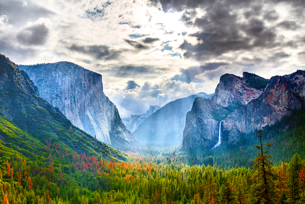 A gorgeous landscape at Yosemite National Park. There are trees in the valley in between large mountains. On one mountain you can see a waterfall on the side of it. It is cloudy but there is sun shinning through the clouds.