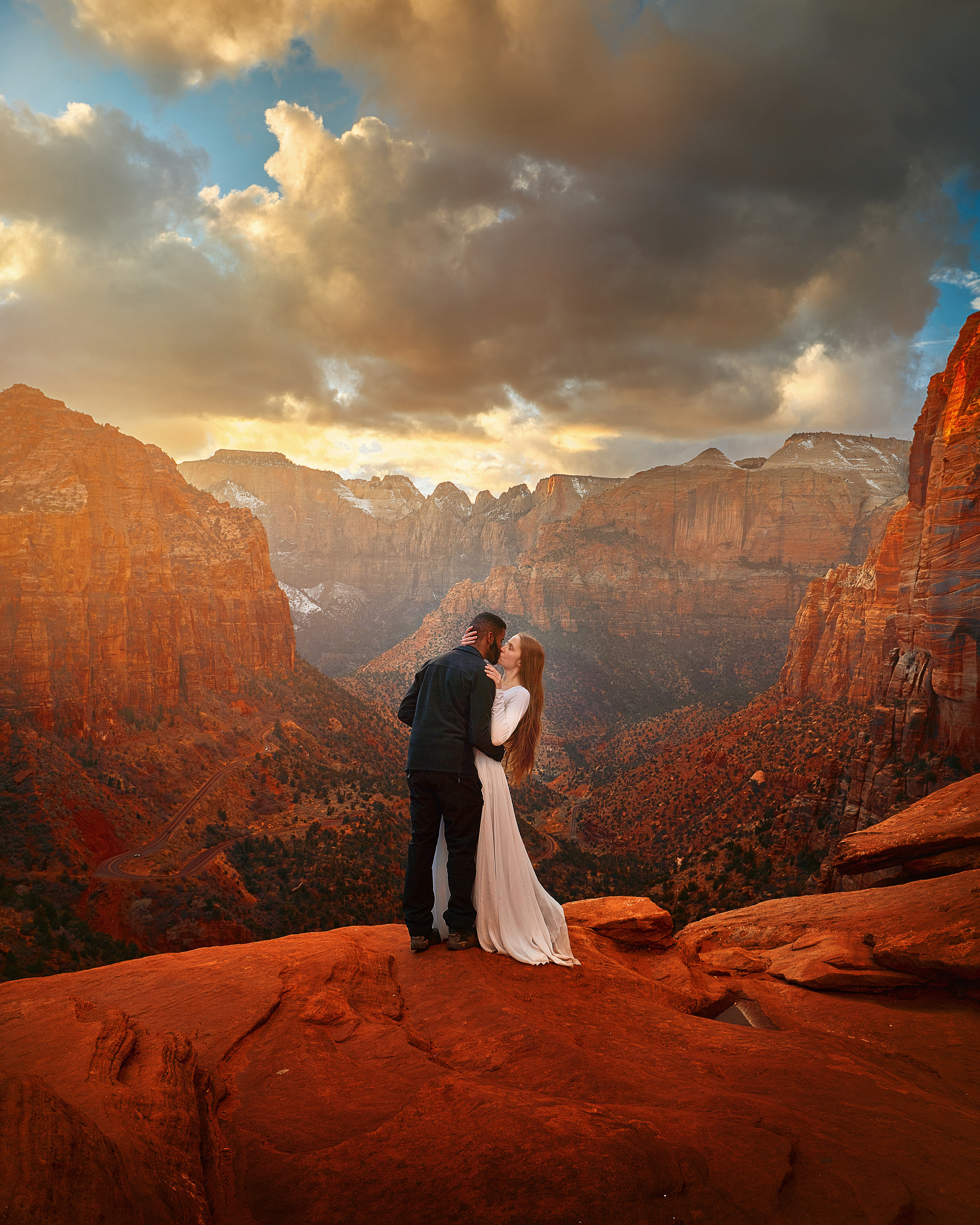 A woman in a long white dress with long hair kissing a man in all black on the edge of a cliff. They are surrounded by red sandstone mountains and rock formations on a cloudy day. You can see snow on some of the mountains.