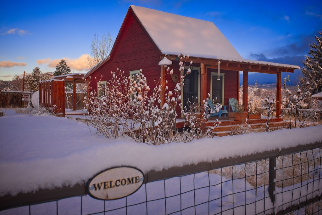 A view of the charming red pioneer cabin, one of the best VRBOs in Utah. Snow has fallen and it is sunset, adding to the quaint farm charm of the Pioneer Cabin.