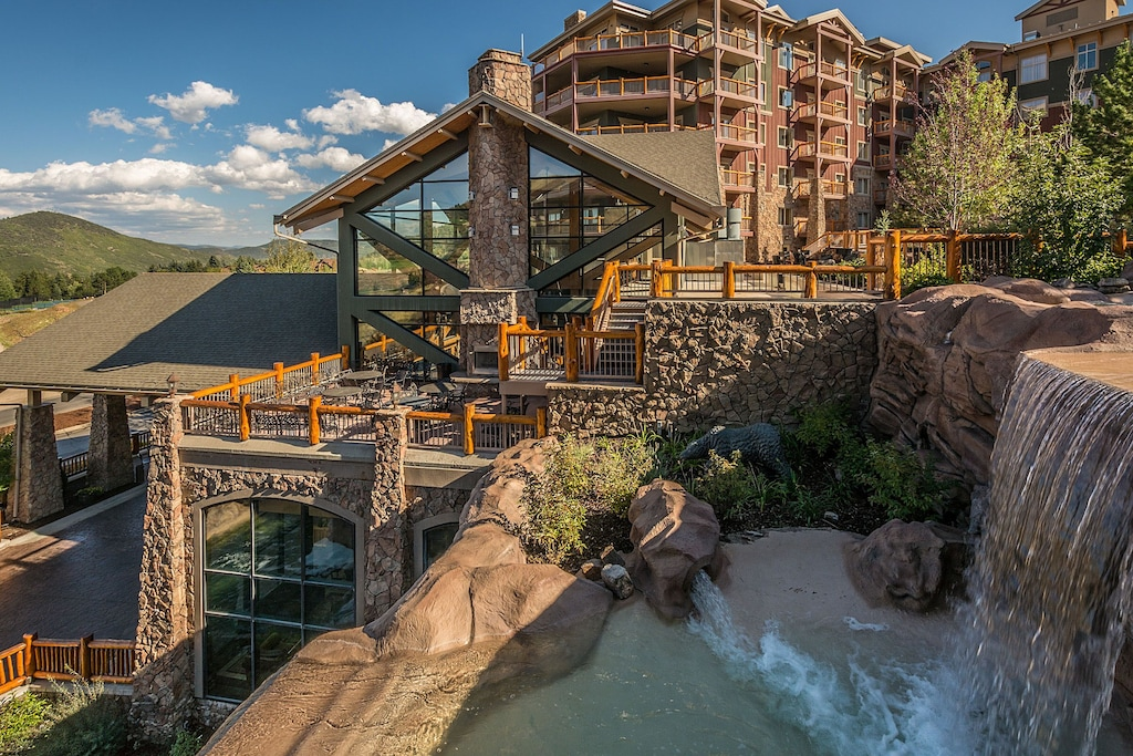 External view of the Westgate Park City resort one of the best vacation rentals in Utah. The view includes the mountains in the background and a manmade large waterfall in the foreground.