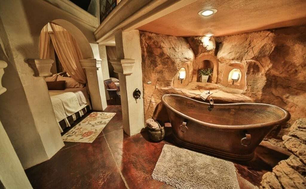 photo of the luxurious hammered metal bathtub in a bathroom styled with red desert rock walls and salt lamps