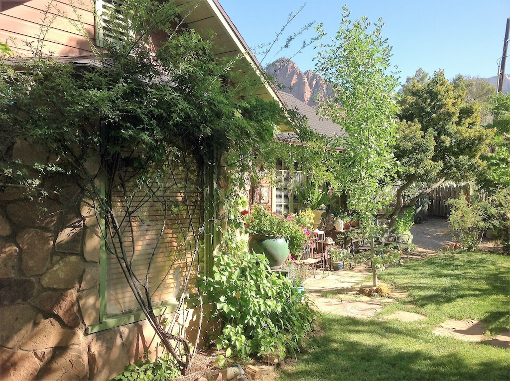 View of the lush garden exterior of the Historic Rose Cottage, one of the best Airbnbs in Utah. You can see the red rocks of Zion National Park behind the cottage.