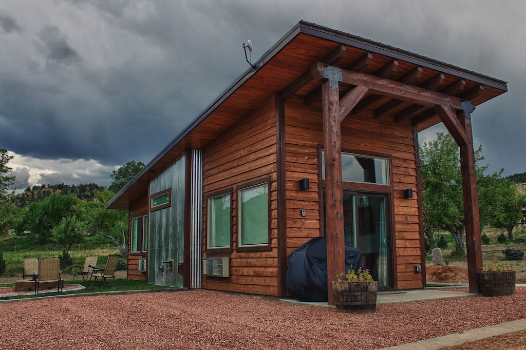 View of the cedar and sheet metal facade of the tiny home. Fire pit with 4 chairs and apple trees are visible. This is one of the best vacation rentals in Utah.