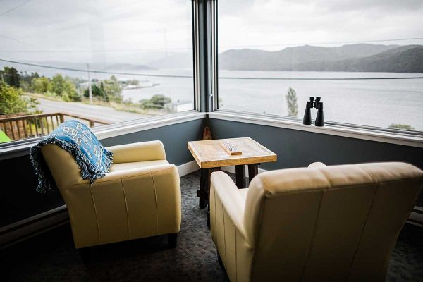 The interior of the lobby of the Bonne Bay Inn. There are two pale yellow leather chairs. The chairs are angled looking out two large windows. Out the windows you can see a bay landscape with hills in the distance. It is one of the best places to stay on a West Newfoundland itinerary.