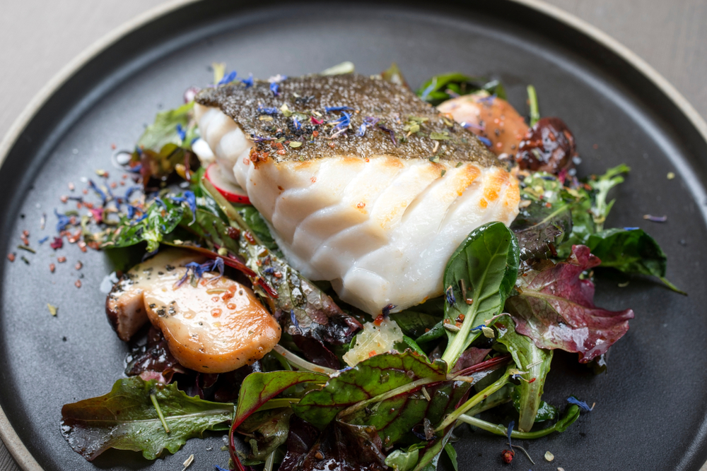 Cooked cod with spices and dried flowers sprinkled on it. It is sitting on a bed of greens with a type of dressing drizzled on it. Everything is on a black plate.