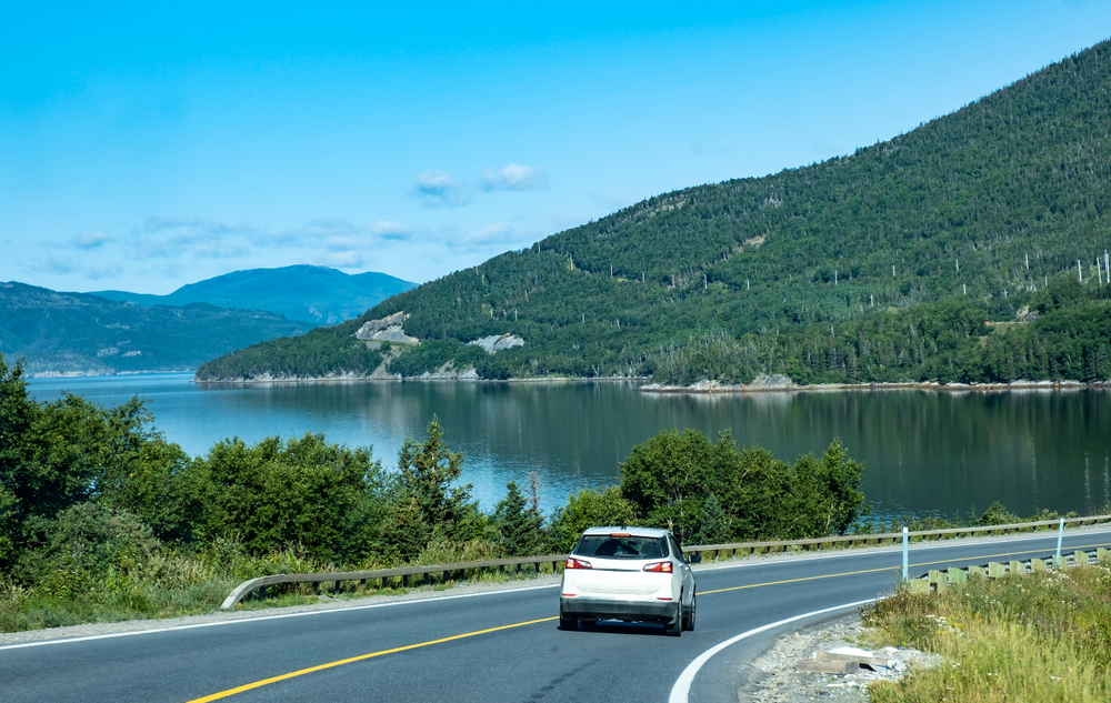 A white car driving on a road that is on the shore of a river or bay. There are hills on the shore of the water that are covered in trees. The sky is clear and blue.