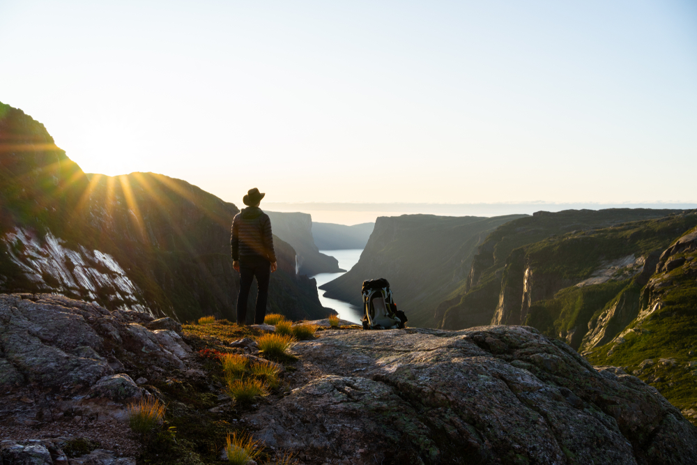 A person standing on a cliff wearing a hat looking out onto a mountain landscape. There is also a backpack next to them on the cliff. The sun is beginning to set behind one of the mountains.