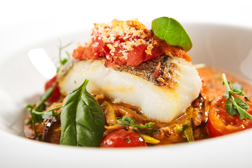 A white plate of cooked halibut. It is sitting in a creamy red sauce with sliced tomatoes, basil, and breadcrumbs sprinkled on top.