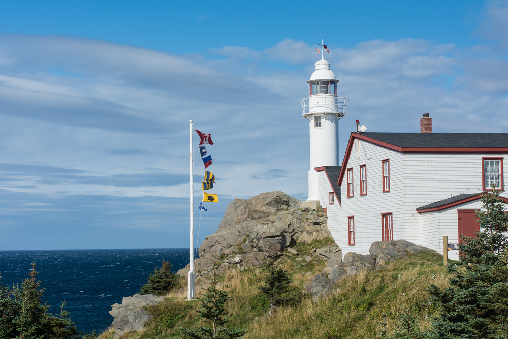 A white lighthouse with red trim looking over the shore at Lobster Cove. There are large rock formations, grasses growing on the rocks, and a flag pole with different types of flags on it. You can just see the water over the rocks.