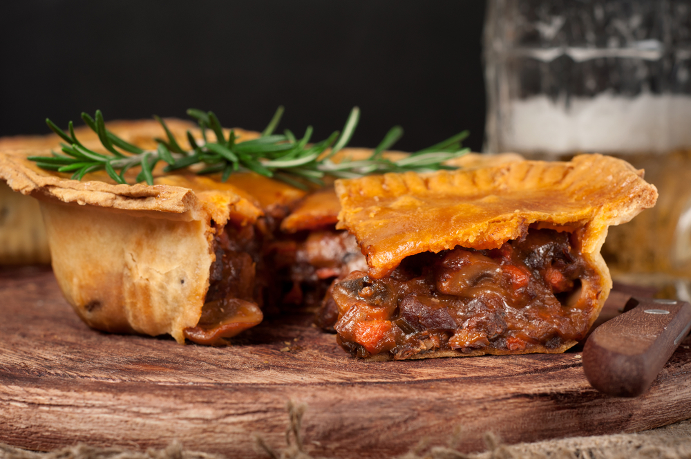A meat pie that is cut open on a wooden board. You can see beef, carrots, mushrooms, and sauce in the pie. On top of it is a sprig of rosemary.