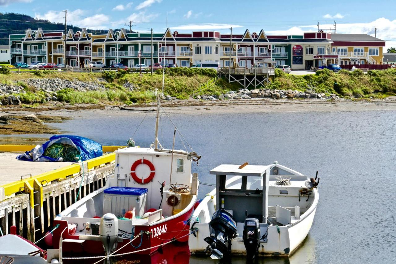 Looking at a large multicolored hotel on a bay in West Newfoundland. It is right on the shore and you can see tall grassy dunes and rocks in the shore. There are also a few boats tied up to a dock across from the hotel.